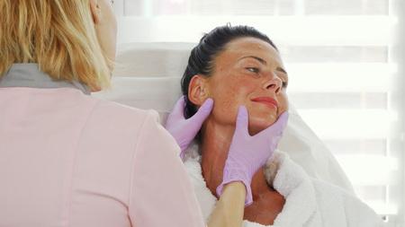 Hermosa mujer madura obteniendo su piel examinada por un dermatólogo profesional. Cosmetóloga examinando el rostro de su clienta antes de brindarle tratamiento. Dermatología, concepto de cuidado de la piel.