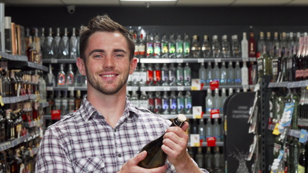Handsome young man smiling to the camera while choosing wine. Young handsome man examining wine bottle at the supermarket while doing groceries. Attractive male customer smiling to the camera while shopping for wine. Drinks, food, lifestyle concept.