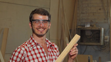 Happy male carpenter posing with a piece of wood at his workshop. Professional carpenter sanding wood at his furniture workshop. Cheerful cabinetmaker holding piece of wood, smiling happily to the camera. Confidence, entrepreneurship, success concept. 免版税图像