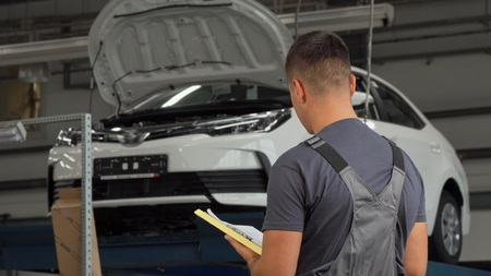 Rear view shot of a car mechanic filling papers. Rear view shot of a professional car mechanic working at the garage, filling papers after repairing automobile on the background. Experienced mechanic writing on his clipboard. Stock Photo