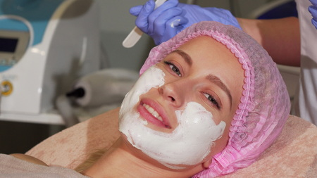 Happy woman smiling during facial mask application at beauty salon. Cropped shot of a woman smiling joyfully to the camera with facial organic mask applied on her face. Beauty salon concept.