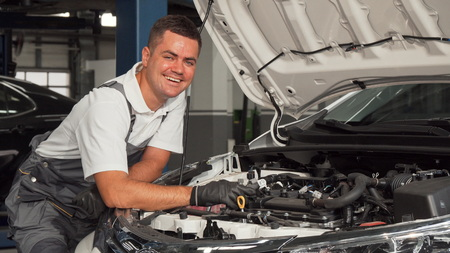 Cheerful mechanic enjoying working at the garage. Young cheerful car mechanic smiling to the camera while examining engine of a car. Professional auto mechanic working at his garage, looking under the hood of a car. Service, driving concept. 版權商用圖片