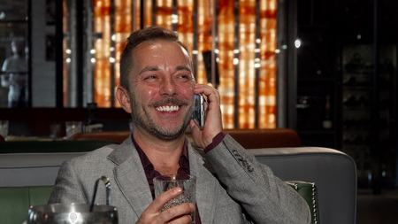 Cheerful businessman drinking whiskey while talking on the phone. Handsome mature man laughing joyfully, using his smart phone at the restaurant. Connection, mobility, success concept.