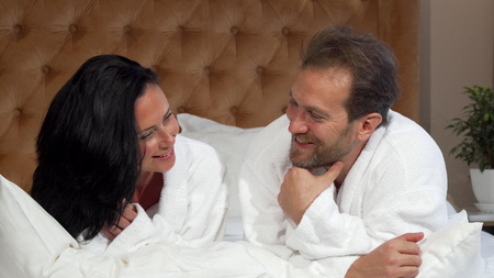 Mature married couple in bathrobes talking, lying in bed at the hotel together. Couple enjoying vacation. Bearded man talking to wife in the morning. Tourism concept Stock Photo
