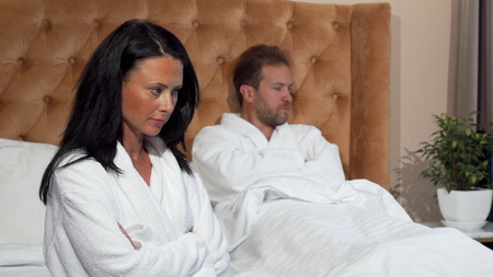 Married couple not speaking after having a fight at hotel room. Woman looking upset, her husband looking at her angrily on the background, copy space. Problems, divorce concept Banque d'images