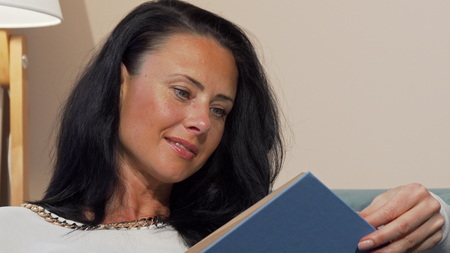Attractive mature woman smiling joyfully reading interesting book. Cropped shot of a beautiful woman relaxing at home, looking surprised reading. Literature, knowledge concept