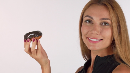 Beautiful red haired woman enjoying smelling delicious chocolate donut. Cropped shot of a gorgeous woman smiling to the camera preparing to eat dessert. Junk food, cheat meal concept