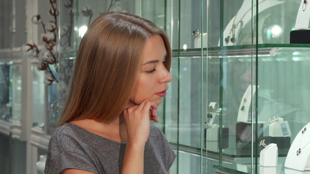 Attractive young female customer examining display at the jewelry store. Beautiful woman looking at the jewelry for sale thoughtfully. Consumerism, retail, sales concept Фото со стока