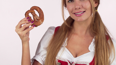 Unrecognizable Oktoberfest woman licking lips hungrily, holding delicious pretzel. Cropped shot of a sexy Bavarian waitress in dirndl licking lips. Hungry, restaurant, pub or bar concept