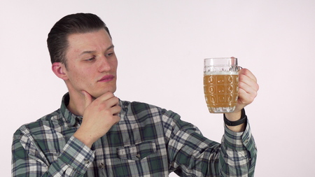 Young man rubbing his chin thoughtfully, examining beer in a mug. Handsome man looking at the beer in a mug doubtfully. Quality check, doubting, examination concept Banque d'images