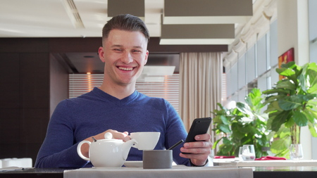 Handsome happy man laughing, using his smart phone at the cafe during breakfast. Attractive young man drinking tea, scrolling feed online. Technology, social media concept