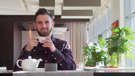 Bearded handsome man looking away thoughtfully, enjoying morning tea. Low angle shot of a happy man smiling joyfully, having tea at the cafe. Lifestyle, relax, happiness concept Stock Photo