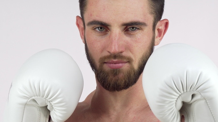 Bearded male boxer smiling to the camera, standing in fighting stance. Confident fighter holding up his hands in boxing gloves, ready to fight. MMA, martial arts, defense concept 免版税图像