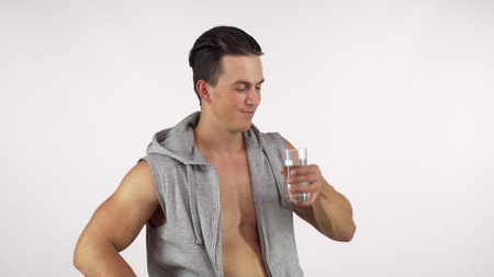 Happy sportsman drinking water after working out at the gym, showing thumbs up. Ripped athletic man resting after exercising, enjoying drinking water. Health, hydration concept