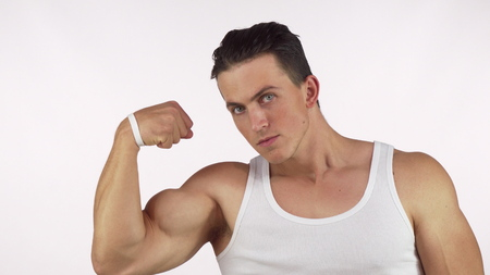 Muscular young man flexing his bicep looking to the camera fiercely. Handsome male bodybuilder showing off his muscles. Athletic man with huge biceps. Sports, determination, lifestyle concept