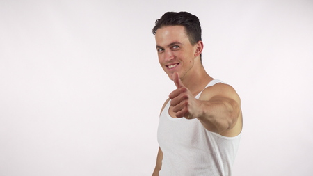 Happy handsome muscular man showing thumbs up, smiling to the camera. Healthy strong man with athletic body gesturing thumbs up. Health, weightloss, gym workout concept