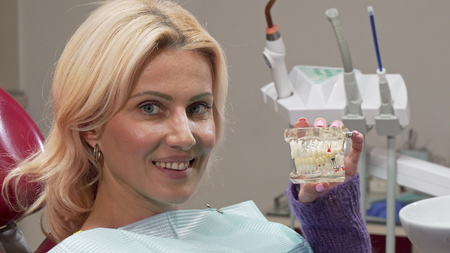 Mature woman smiling to the camera, holding dental mold at the clinic. Attractive female patient examining teeth model, waiting for dentist at the clinic. Health care concept Archivio Fotografico - 117933936