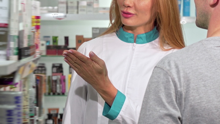 Female pharmacist helping customer, pointing at the shelf with medications. Cropped shot of a drugstore worker smiling, talking to the client. Saleswoman, retail concept