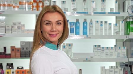Rear view shot of a female pharmacist working at the drugstore. Long haired female chemist smiling to the camera over her shoulder after examining shelves with products
