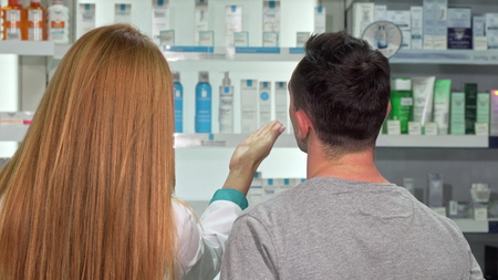 Rear view shot of a pharmacist and customer talking at the drugstore. Man shopping at the pharmacy, asking chemist for an advice. Female drugstore worker helping male client Imagens