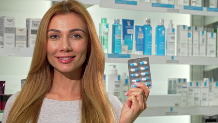 Lovely happy woman holding blister of pills, smiling at the pharmacy. Cheerful attractive female customer shopping at drugstore, holding vitamins pack, copy space. Healthcare concept