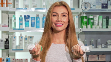 Happy beautiful woman smiling to the camera, shopping at pharmacy. Lovely cheerful female customer choosing between two products at the drugstore. Purchase, sales concept