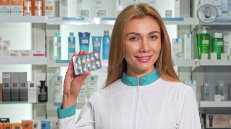 Beautiful female pharmacist smiling, holding blister of capsules at drugstore. Cheerful drugstore worker selling vitamins, smiling joyfully. Friendly customer service concept