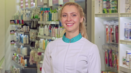Cheerful female pharmacist crossing her arms, posing proudly at her drugstore. Attractive female chemist enjoying working at the pharmacy. Confidence, entrepreneurship concept