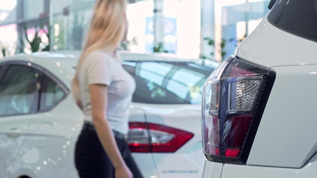 Woman choosing new car at the dealership, copy space. Selective focus on a car light on the foreground, blond female customer examining cars on sale. Driving, ownership concept Imagens