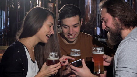 Group of friends having fun at beer pub, using smart phone. Two men and their female friend laughing joyfully watching something funny online on a phone. Technology concept