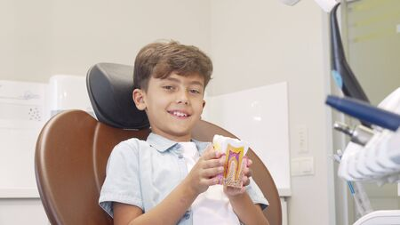 Cute young boy smiling to the camera, holding tooth model. Adorable little boy examining tooth model, sitting in a dental chair. Healthy teeth concept