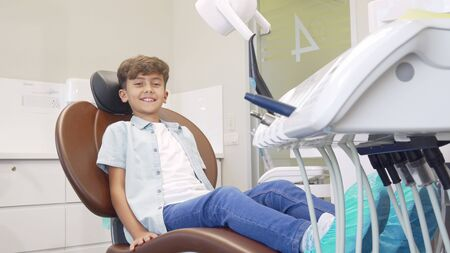 Lovely young boy sitting in dental chair waiting for teeth examination. Full length shot of a charming little boy smiling to the camera, waiting for the dentist at the clinic