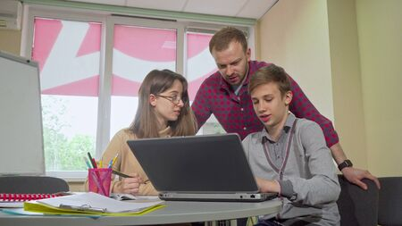 Male teacher helping his teenage students with a project at school. Two young teen students working on a project together, teacher helping with assignment