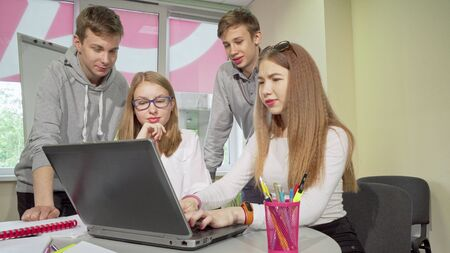 Group of teenagers discussing assignment, studying together at school. Lovely teenage girls talking, working on assignment on the laptop, boys chatting on the background Archivio Fotografico