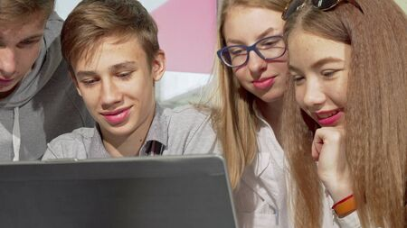 Teenage boy using laptop at school, studying with his classmates. Cropped shot of a group of teenagers working on a project online. High school friends discussing assignment