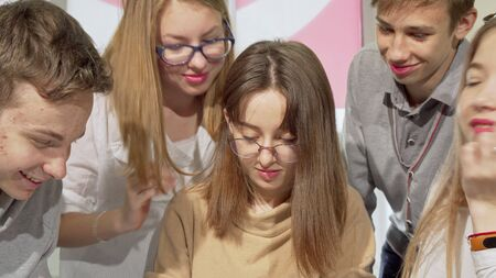 Teenage girl writing in her textbook with her classmates surrounding her. Sliding cropped shot of a lovely teen female student doing homework with her school friends