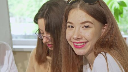 Sliding shot of three teenage female students working on a project at school. Cropped shot of a cheerful teen girl smiling to the camera while studying together. Education concept Archivio Fotografico