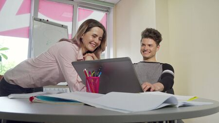 Young college couple enjoying studying together. Beautiful younf female student talking to her boyfriend while using laptop at classroom together. University friends studying