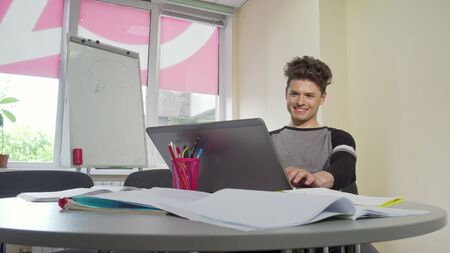 Young male college student smiling, typing on his laptop. Thoughtful male student, working on his graduation project online, typing on computer. Education, knowledge concept