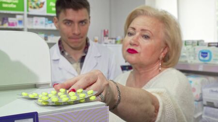 Senior woman asking pharmacist about medicine she is buying. Selective focus on blisters of pills, elderly female customer asking chemist an advice on the background