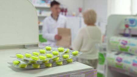 Pharmacist talking to senior client, pills blisters on foreground. Selective focus on pills, elderly woman talking with chemist at the pharmacy on the back, copy space Stock fotó