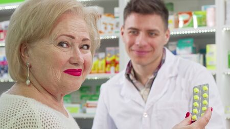 Rear view shot of a senior woman smiling to the camera after buying medicine. Cropped shot of an elderly female customer smiling, holding blister of pills at drugstore