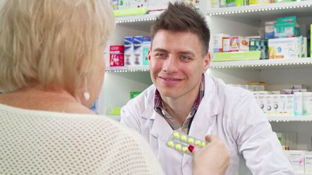 Cheerful pharmacist selling medication to senior customer. Handsome friendly chemist giving pills to an elderly client. Unrecognizable senior woman buying medicine Archivio Fotografico