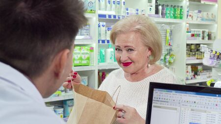 Senior woman buying medical products at pharmacy, looking in a shopping bag. Lovely elderly female customer checking her purchase in a paper shopping bag, smiling at pharmacist