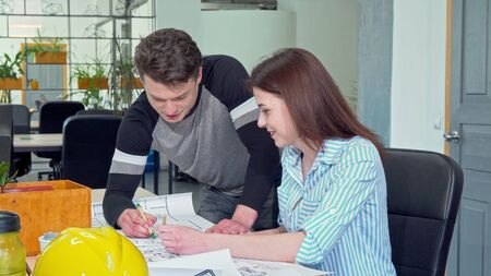Lovely female architect smiling to the camera, working with her colleague. Two young engineers discussing blueprint. Architects working on a construction plan