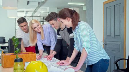 Young architects working together on a blueprint at the office. Group of skilled engineers working on a construction project together. Architecture, development concept