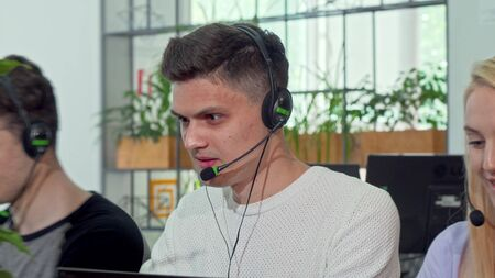 Young man working at customer support call center, wearing headset. Handsome male call center worker typing on computer. Friendly male operator helping customers online