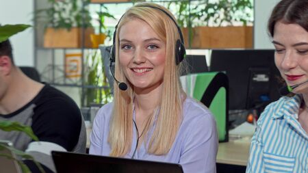 Charming young woman smiling to the camera, working at call center. Attractive female customer support worker working on computer, answering clients calls. Technical support concept