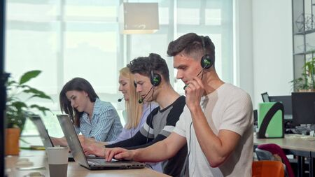 Friendly young man smiling to the camera, working at customer support call center. Attractive male technical support operator wearing headset with microphone, smiling cheerfully