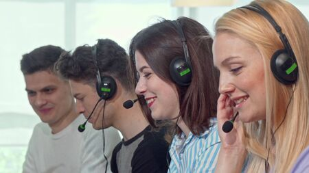 Group of young people wearing headsets, working at call center. Cheerful young female technical support operator smiling to the camera. Customer support agents answering calls Archivio Fotografico